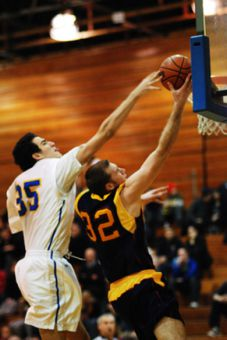 6'6'' Queen's forward Mitch Leger scores against 6'10'' Ryerson centre Joseph Imbrogno.