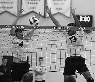 Queen's setter Devon Miller (4) makes a block Friday as teammate Michael Amoroso looks on.