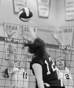 Setter Ellen Gray (11) and teammate Colleen Ogilvie go up for a block Friday against Western outside hitter Elaine Screaton.
