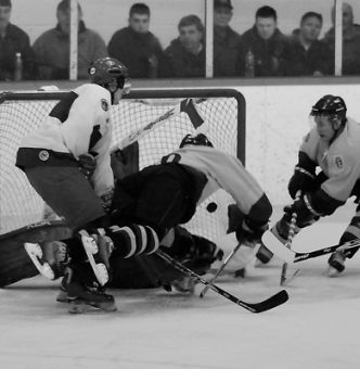 Jon Asselstine emulates Bobby Orr's famous flying pose as Jeff Ovens (20) sets to knock home the rebound for Queen's second goal Wednesday against RMC at Constantine Arena. The Carr-Harris Cup victory also clinched a playoff berth for the Gaels.