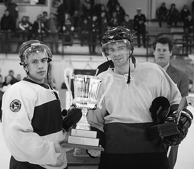 Queen's forward Jon Lawrance and RMC's Richard Lim pose with the game's MVP trophy.
