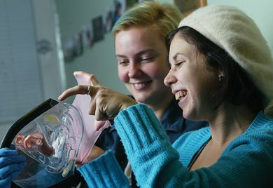 SHRC director Kat Heintzman and Morgan Vanek demonstrate the use of a dental dam, which the centre sells for $1.