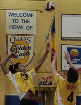 Devon Miller (4) sets Queen's rookie middle hitter Michael Amoroso up for a kill against Ryerson Saturday night in Bartlett Gym.