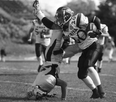Queen's defensive back Addison Rich does a faceplant in a Sept. 29 football game against Laurier. The football team would likely receive more funding if the University follows through on the Athletics Review's recommendations.