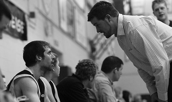 Queen's assistant coach Duncan Cowan speaks to point guard Baris Ondul in a Feb. 2 game.