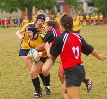 Queen's Breanne Sherwood is tackled in Sunday's rainy exhibition match against the Carleton Ravens as teammate Catherine Foster looks on. The Gaels beat the Ravens 32-8.