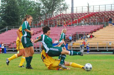 Queen's striker Renee MacLellan (14) takes out Marie-Michelle Sullivan of the Trent Excalibur with a sliding tackle Saturday.