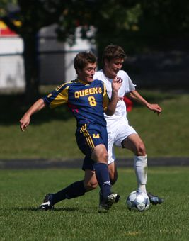 Queen's midfielder Mike Arnold (8) battles Laurentian striker Davor Alisic for the ball Sunday.