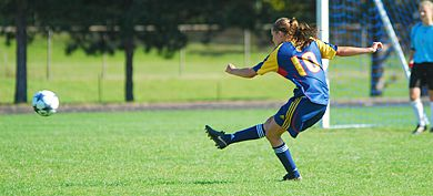 Queen's defender Brie Shaw clears a loose ball Sunday as goalkeeper Katie McKenna looks on.