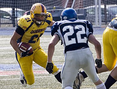 Gaels' running back Mike Giffin tries to juke past Toronto defensive back Derek Batchelor Saturday. Queen's won 58-14.