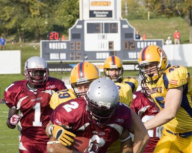 Queen's linebacker Chris Smith tackles Ottawa's Chayce Elliot Saturday as Stephen Laporte (45) comes to help.