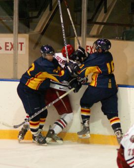 Gaels' forwards Jon Lawrance and Jeffrey Johnstone plough York defenseman Bill Siekris into the boards Friday at the Memorial Centre. The Gaels lost 3-0.