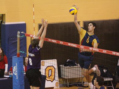 Gaels' outside hitter Joren Zeeman (5) goes for a kill against Western's Reid Halpenny Saturday.