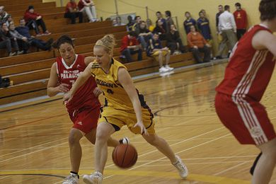 Gauley drives against the Paladins' Carolyn Pumphrey (7) and Jackie Geiger. Queen's won 79-64.