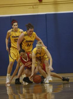 Gaels Lyndsay Gauley (4) and Anne Murphy (14) scramble for a loose ball against RMC's Sharlene Harding Wednesday night at Bartlett Gym.