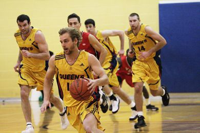 Gaels' guard Ryan Hairsine dribbles up court against York Friday with teammates Scott Stinson (15), Mitch Leger (14) and Nick DiDonato (9) following. Queen's won 72-68.