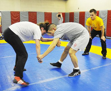 Queen's wrestling coach Jamie Macari (right) looks on as two of his athletes practice Wednesday in the PEC.