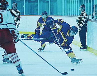 Gaels' forward Brock Ouellet (27) tries to stay on his feet Friday while shooting the puck in past RMC's Logan Oversby as teammate Brandon Perry (17) looks on. Queen's beat the Paladins 4-3 in a shootout.