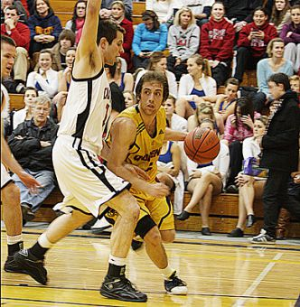 Queen's guard Baris Ondul drives against Carleton's Elliott Thompson Saturday night. The Ravens beat the Gaels 100-75.