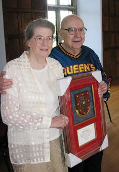 Dr. Alfred Bader and his wife Isabel pose with a gift they received from Principal Tom Williams.