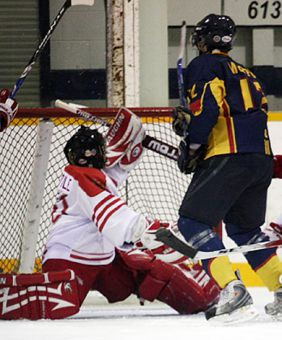 RMC goaltender Brendan Boyle stretches to save Queen's forward Chris Murphy's effort.