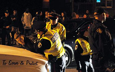 Kingston police make one of their 60 arrested Saturday night.