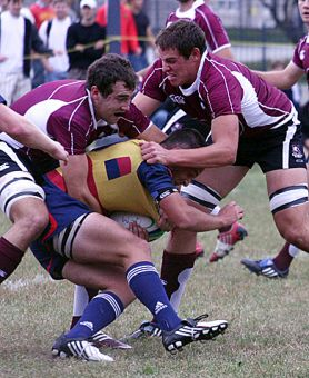 Gaels scrum-half Calum Ramsay gets hauled down by two McMaster players during Saturday's shellacking of the Marauders at Kingston Field.