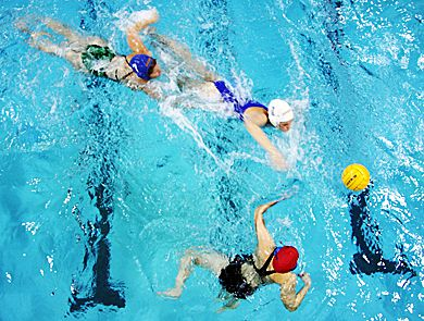 two water polo players chase the ball while the goalie (bottom) tries to get in the way.