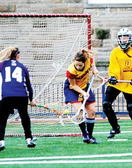 Goaltender Freyah Durand keeps an eye on the action while attack Jackie Byers scoops the ball away.