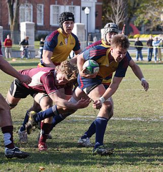 Gaels' lock Ryan Kruyne drags a McMaster defender for a ride during Saturday's 17-8 win at Kingston Field.