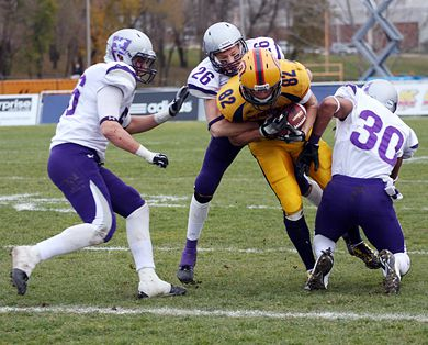 Receiver Scott Valberg protects the ball while three Mustang defenders pull him to the ground.