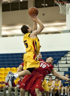 Gaels' guard Baris Ondul climbs over RMC guard James Byun during Saturday's 83-70 win over the Paladins.