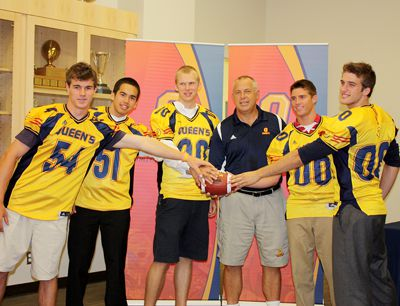 Football head coach Pat Sheahan is surrounded by the 2010 local recruiting class at the Queen's Centre during their introduction to the media.