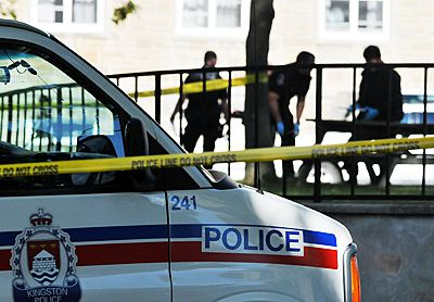 Kingston Police investigate the scene of a deceased student behind Victoria Hall yesterday morning.