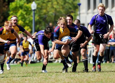 Queen's hooker Mason Curtis tries to escape Western's grasp in men's rugby's 31-15 loss to the Mustangs on Saturday.