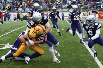 Running back Jimmy Therrien is tackled to the ground by the Mustangs.