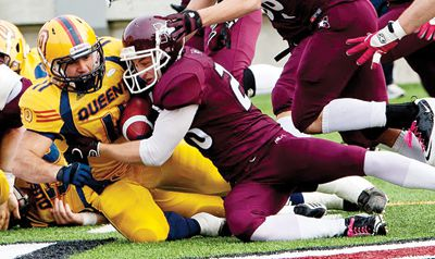 Gaels running back Jimmy Therrien tries to fend off a barage of McMaster Marauders.