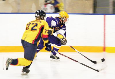 Forward Kelsey Thomson races for the puck against a Laurier player in their 3-1 loss Saturday.