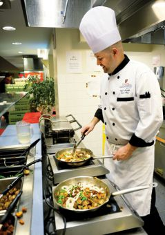 Sous chef Nigel Hughes prepares vegan food at Leonard Cafeteria, which features a vegan station for students.