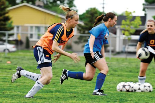 Queen's striker Jacqueline Tessier chases down a teammate during a Kingston FC training session.