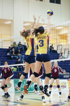 Women's volleyball players go up for a block during their straight-set win over the McMaster Marauders on Saturday night.