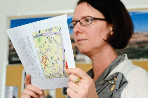 Queen's professor of film and media Dorit Naaman holds up two maps of Qatamon, one hand drawn by Hala Sakakini.