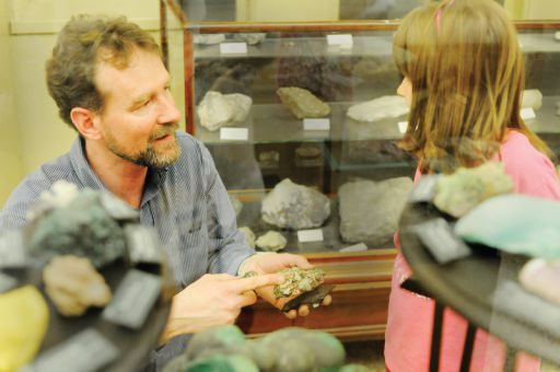 Curator Mark Badham shows an elementary school student a mineral sample during her Girl Guide troop's visit to the Miller Hall museum.