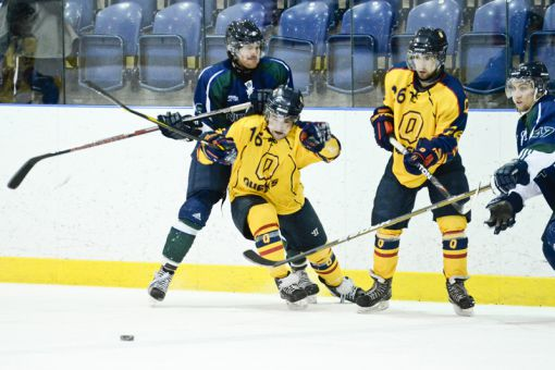 Gaels forward Kelly Jackson (left) gets taken down from behind during a 6-4 loss to the Nipissing Lakers on Saturday night.