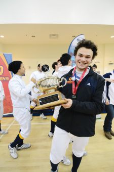 The men's fencing team's sabre captain poses with the OUA team trophy after Sunday's tournament.