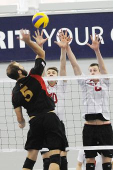 Frédéric Mondou (5) of the Laval Rouge et Or blocks a hit by Allen Meek (10) of the Calgary Dinos at the 2012 CIS men's volleyball championship.