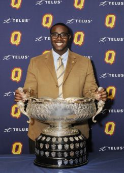 Football defensive lineman Osie Ukwuoma smiles with the Jenkins Trophy for outstanding male student-athlete.