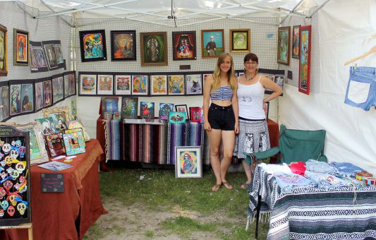 Artist Sherri Nelson (right) stands with her daughter at the Skeleton Park Art Festival. Nelson says her art is inspired by death.