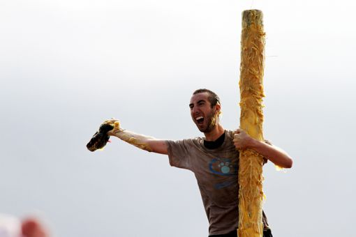 Jordy Jacob, Sci '16, captures the tam on Saturday's Grease Pole event.