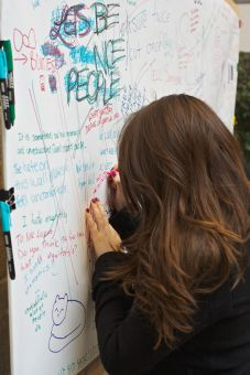 A student writes on the Free Speech Wall, which was taken down last April.